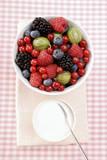 Fresh summer berries in white bowl, sugar beside it