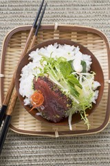 Raw tuna fillet with poppy seeds, rice and salad