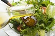Pouring olive oil into wooden spoon above salad leaves
