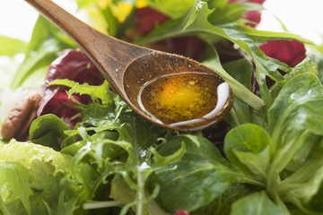 Olive oil in wooden spoon above salad leaves