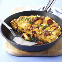 Potato tortilla with chorizo in frying pan