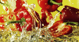 Peppers falling into water against yellow background