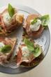 Crostini with Parma ham, mozzarella and basil