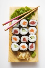 Maki sushi with fish and cucumber on sushi board