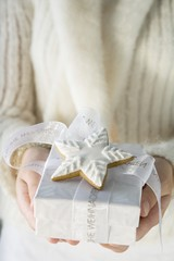 Woman holding Christmas gift with cinnamon star