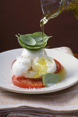Drizzling insalata caprese with olive oil