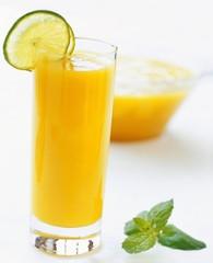 Orange juice garnished with slices of lime