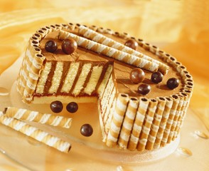 Chocolate cream cake with wafer rolls