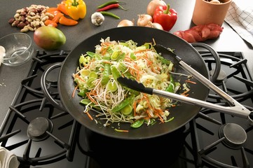 Vegetables in wok on hob, Asian ingredients behind