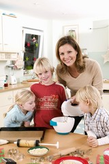 Mother and three children in kitchen baking biscuits