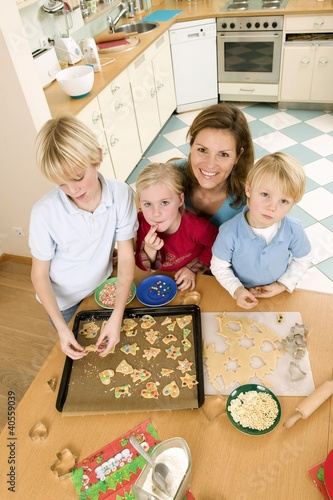Mother and three children baking biscuits