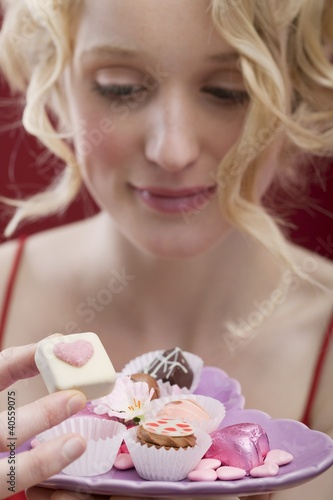 Young woman eating chocolates and sweets