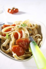 Linguine with cherry tomatoes in heart-shaped dish