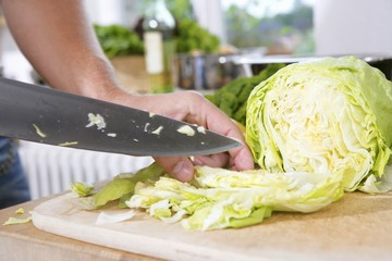 Cutting iceberg lettuce into bite-sized pieces