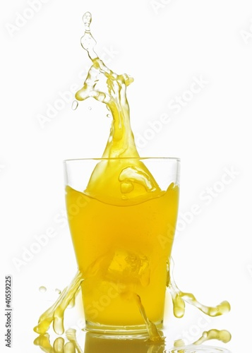 Orangeade splashing out of a glass