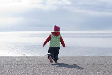 Kleinkind läuft zum Meer
