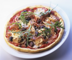 Pizza topped with prosciutto, olives, capers and rocket
