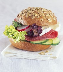 Oat roll filled with salami, Brie and salad