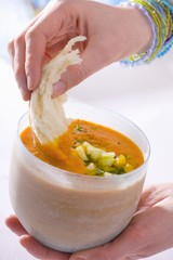 Dipping bread into gazpacho