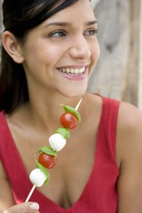 Young woman with tomato and mozzarella skewer