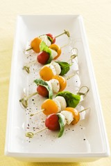 Tomatoes, mozzarella and basil on cocktail sticks