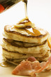 Pouring maple syrup over pancakes, butter and bacon