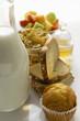 Breakfast ingredients: baked goods, muesli, fruit, milk, honey