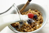 Pouring milk over crunchy muesli with berries in bowl