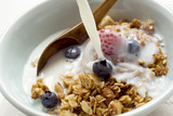 Pouring milk over crunchy muesli with berries