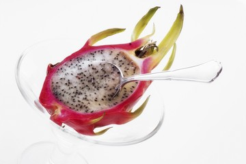 Half a pitahaya in glass bowl with teaspoon