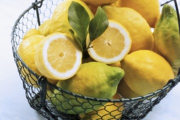 Organic lemons in a wire basket, one halved