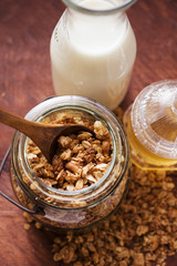 Crunchy muesli in a jar, honey and milk bottle beside it