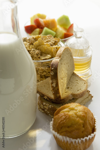 Breakfast ingredients: baked goods, muesli, fruit, milk, honey