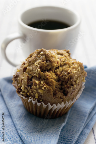 Muffin in front of a cup of coffee