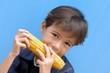 Small boy biting into a corncob