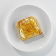 A slice of toast with butter and marmalade on a plate