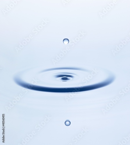 Drop of water falling into water and making ripples