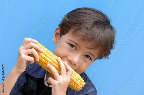 Small boy biting into a corncob