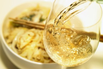 Pouring a glass of wine, noodle dish in background