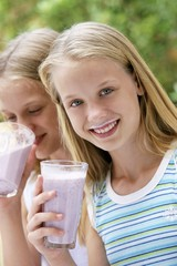 Two girls drinking berry smoothies