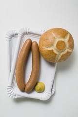 Sausages with mustard and roll on two paper plates