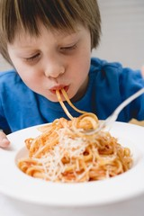 Small boy eating spaghetti with tomato sauce