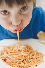 Small boy eating spaghetti