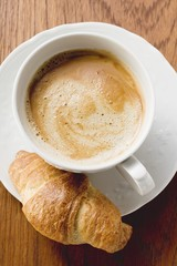 A cup of cappuccino with a croissant