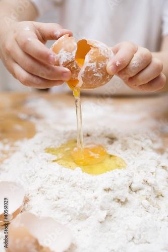 Child breaking an egg onto a heap of flour