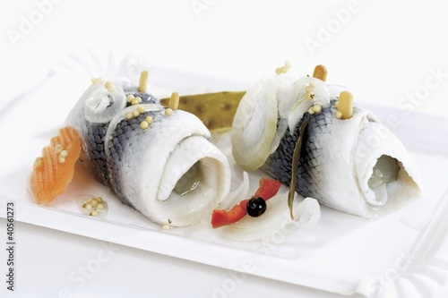 Two rollmops on a paper plate