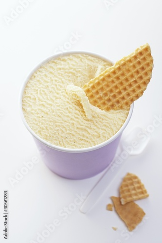 A tub of vanilla ice cream with wafer