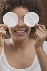 Young woman holding two cosmetic pads in front of her face