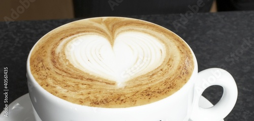 A cup of cappuccino with milk foam decorated with heart