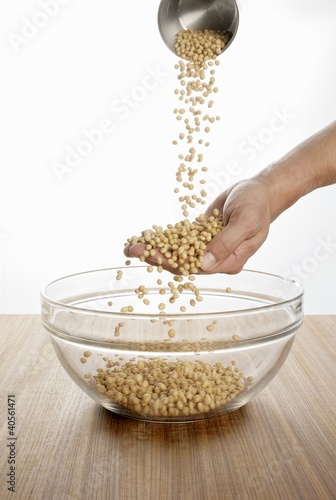 Someone pouring soya beans over their hand into a glass bowl